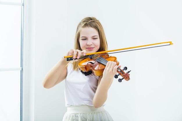창문이있는 흰색 방에서 아름답고 행복하게 공부하기 위해 바이올린을 연주하는 어린 소녀