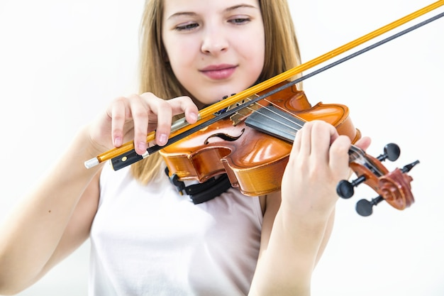 Детская девочка, играющая на скрипке, учится красивой и счастливой на белой поверхности
