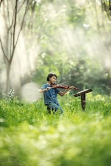 Child girl playing the violin to study at thailand