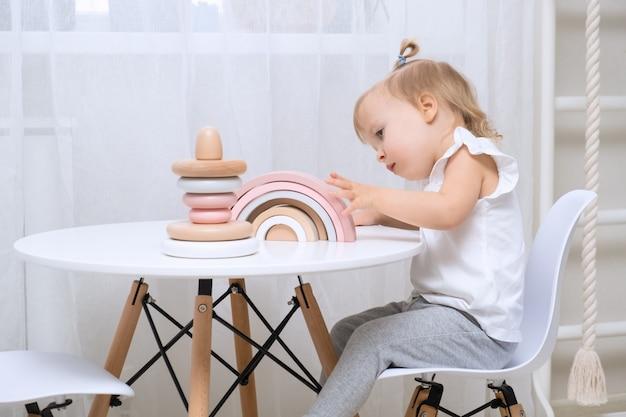 テーブルで木のおもちゃで遊ぶ子供の女の子。自然なおもちゃを持つ小さなかわいい女の子。