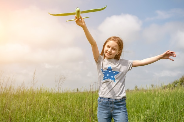 Child girl playing with toy plane outdoors in the field preteen kid launching airplane