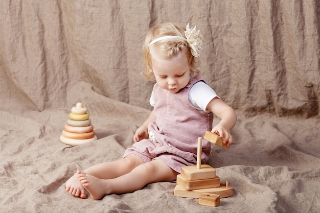 Child girl playing with a wooden toy pyramid. little cute girl with  natural toys.