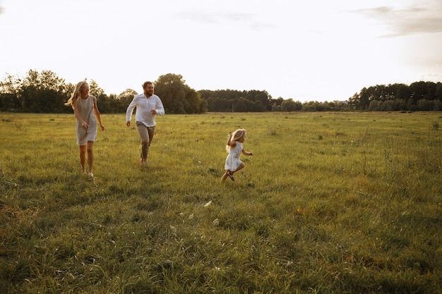 Child girl plays with parents in the summer on a walk. run