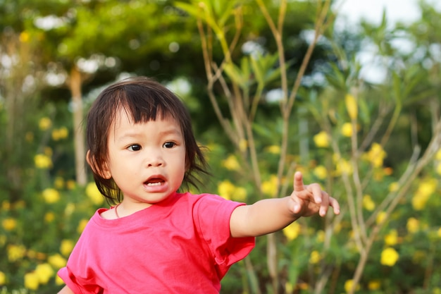 A child girl pointing her finger to the left at the garden.