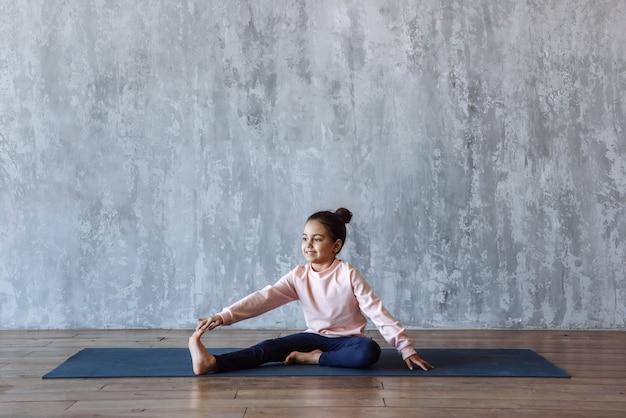 매트에 바닥에 앉아 요가 연습 아이 소녀