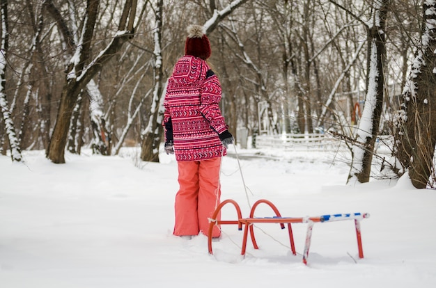 Child girl pull sled on snow in winter park. back of the kid between trees in cold nature.