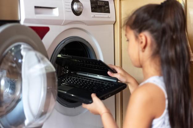 Девушка ребенка положить ноутбук в стиральную машину.