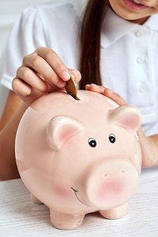 Child girl putting coin into pink piggy bank.