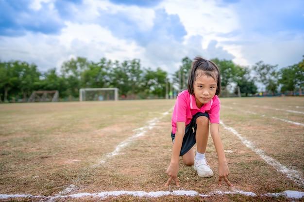 夏のスポーツシーズンにレースを実行している子の女の子