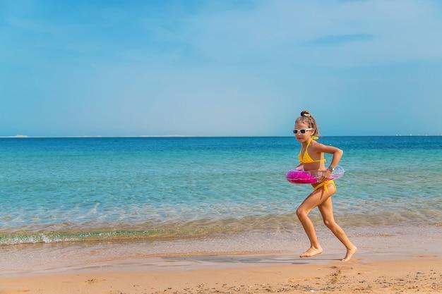 A child girl runs along the beach