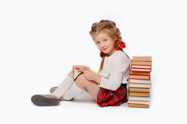 Child girl in school uniform with a book in her hands sitting isolated on a white background