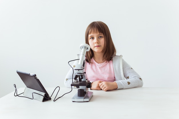 Child girl in science class using digital microscope. technologies, children and learning concept.