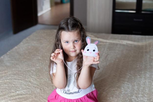 子供の女の子は、ベージュの毛布の上でベッドの上に座っているフェルトでできたおもちゃを縫います。裁縫