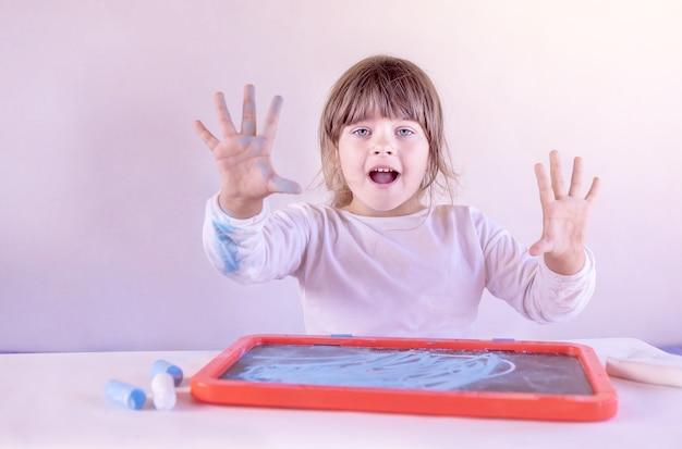 Девочка показывает руки, размазанные цветными мелками