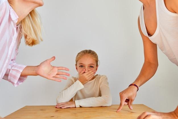 부모가 집에서 논쟁하는 동안 자식 소녀는 닫힌 입으로 앉아, 꼬마 소녀는 카메라를보고 우울하고 무서워합니다.