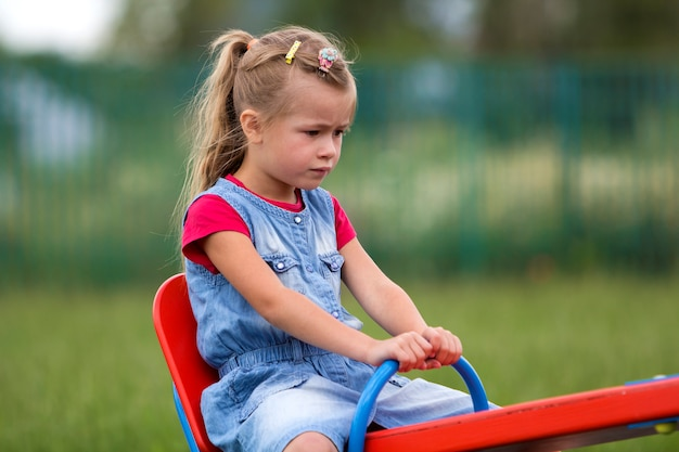 Child girl sits on a swing