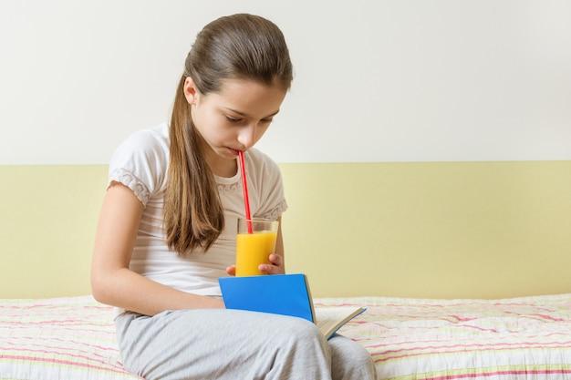 Девушка ребенка сидя дома в кровати с стеклом книги чтения свежего апельсинового сока