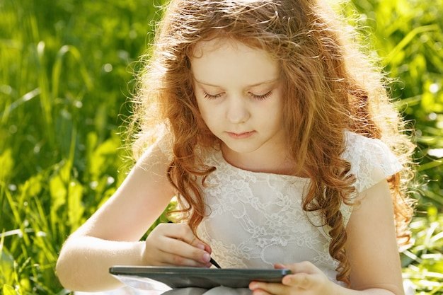 Child girl sitting on grass and playing tablet pc