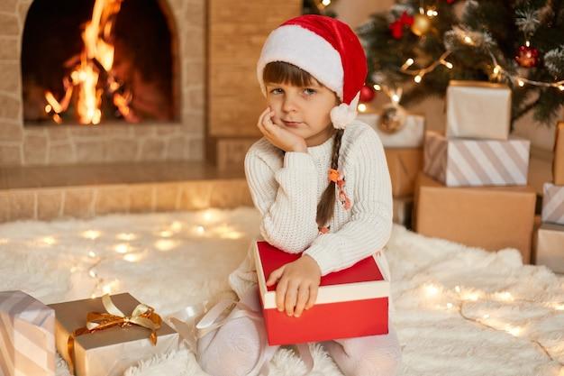クリスマスイブにクリスマスツリーと暖炉の近くに座って、膝にギフトボックスを持って、物思いにふける表情でカメラを見て、サンタの帽子とジャンパーを着て、あごの下に手を保ちます。