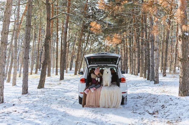 Child girl sitting in the trunk of car with her pet, a white dog samoyed, in winter in snowy pine forest, a girl drinking tea from a thermos