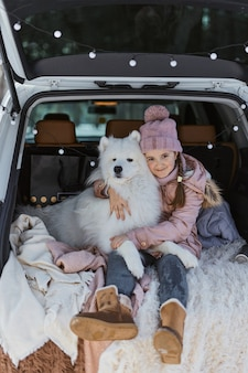 Child girl sitting in the trunk of car with her pet, a white dog samoyed, in winter