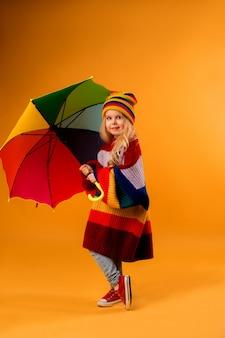 Ребенок девочка улыбается в яркий разноцветный свитер и шляпу, держа зонтик стоит на желтом пространстве
