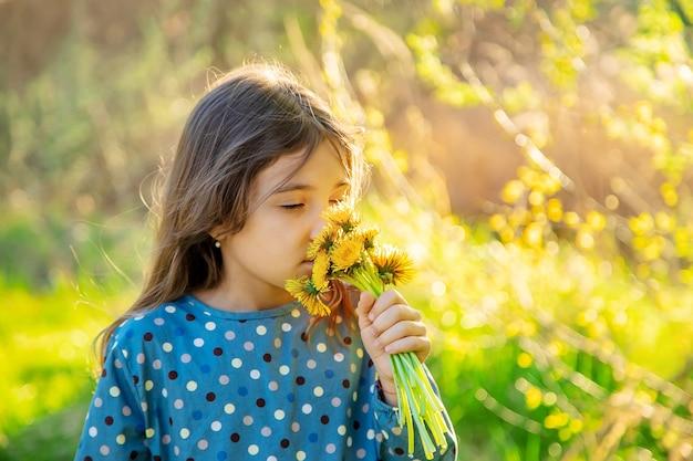 Ребенок девочка нюхает цветы одуванчика
