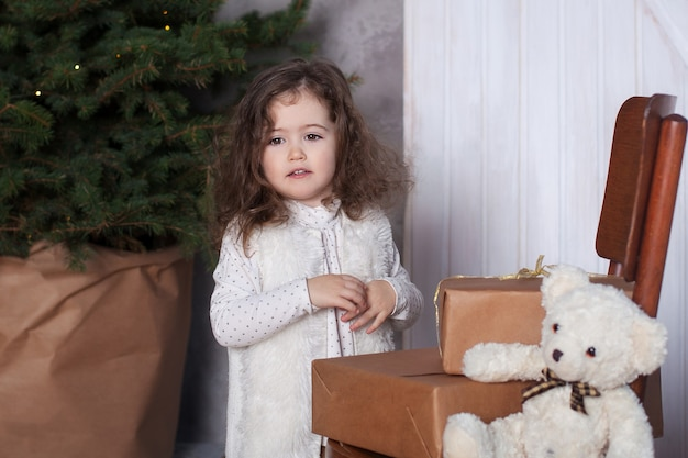 Child  girl stands next to gifts on chair on christmas in living room