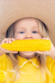 Child girl in a straw hat eating corn
