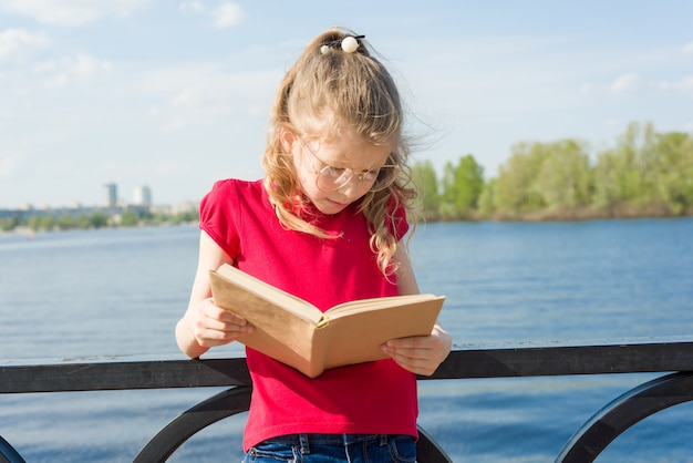 Child girl student wearing glasses reading book
