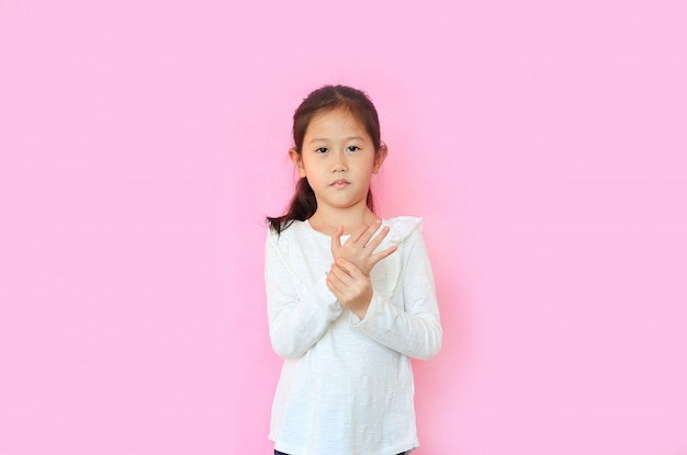 Child girl suffering pain on hands and fingers on pink background
