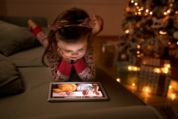 Child girl talking to grandparents by video call on tablet on christmas eve at home
