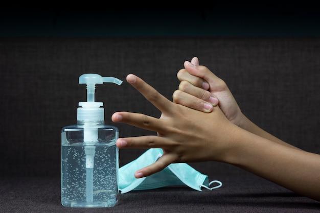 Ребенок девочка использует дезинфицирующее средство для рук, чтобы очистить ее руку.