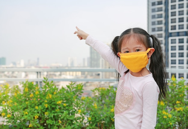 Child girl wearing protection mask with pointing up.