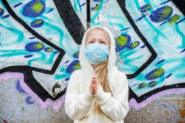Child girl wearing respirator mask asks for help