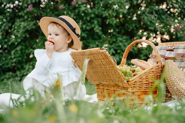 A child girl in a white dress and hat sits on a blanket with a basket in the park eats fresh strawberries the daughter is having breakfast in the meadow in the field
