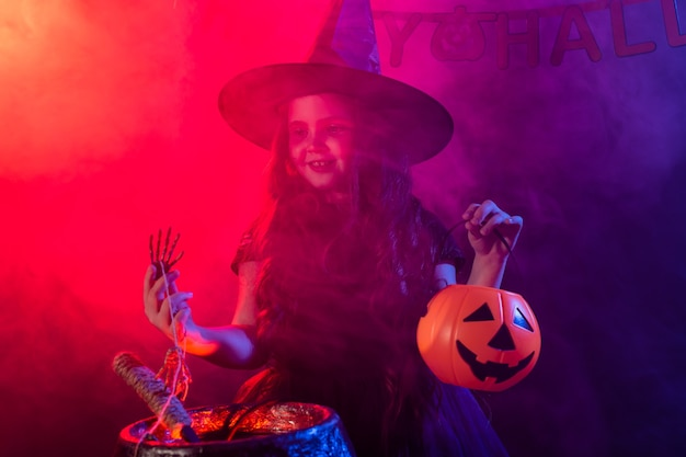 할로윈 휴일에 가마솥에서 물약을 준비하는 어린 소녀 마녀