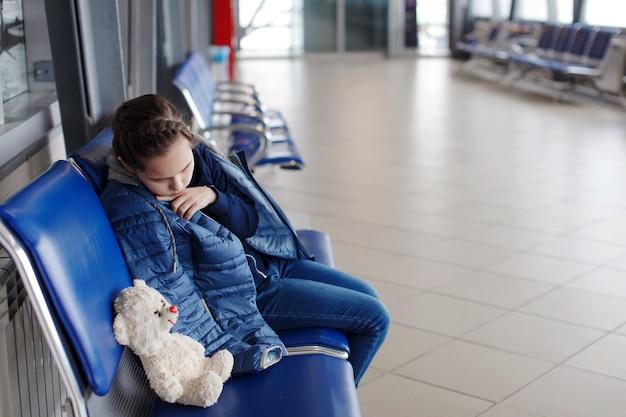 青いアームチェアで眠っていて、飛行時間を待っている窓の近くの空港でおもちゃのクマを持つ子供の女の子
