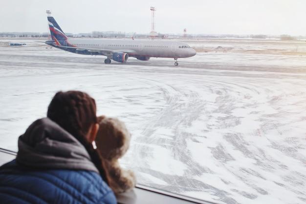 窓の近くの空港でおもちゃのクマを持つ子供の女の子は飛行機を見て、飛行時間を待ちます