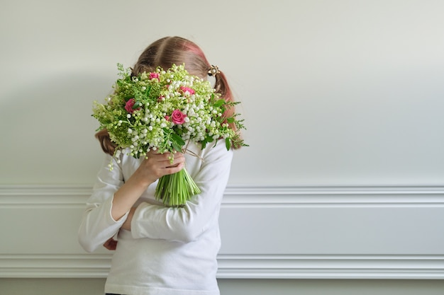 Child girl with bouquet of beautiful spring flowers, face covered with bouquet