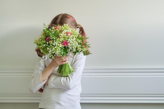 Ребенок девочка с букетом красивых весенних цветов, лицо покрыто букетом