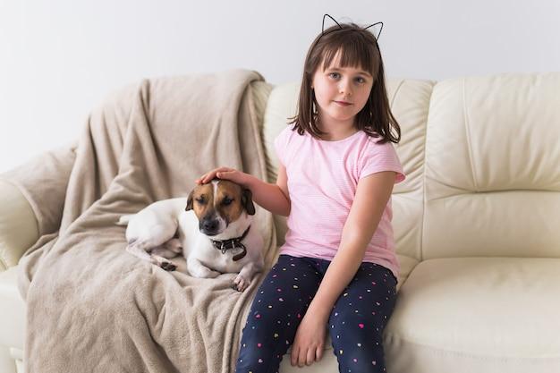 かわいい犬のジャックラッセルテリアとソファの上の子の女の子
