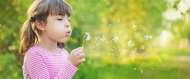 公園でタンポポと子供の女の子。セレクティブフォーカス。