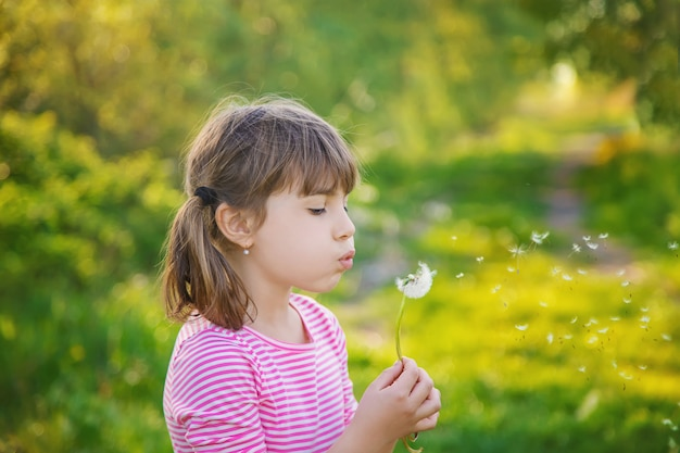 Child girl with dandelions in the park. selective focus.