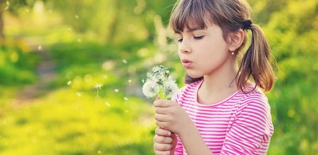 Child girl with dandelions in the park