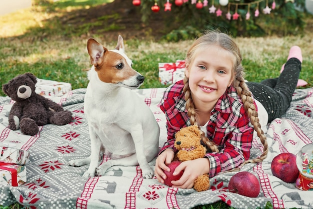 Child girl with dog jack russell terrier near the christmas tree with gifts,