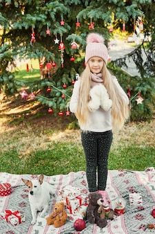 Child girl with dog near the christmas tree with gifts