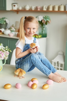 Child girl with easter eggs and chickens in kitchen. happy easter concept. happy family preparing for easter.