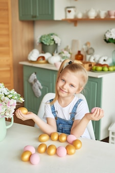 Child girl with easter eggs in kitchen. happy easter concept. happy family preparing for easter.