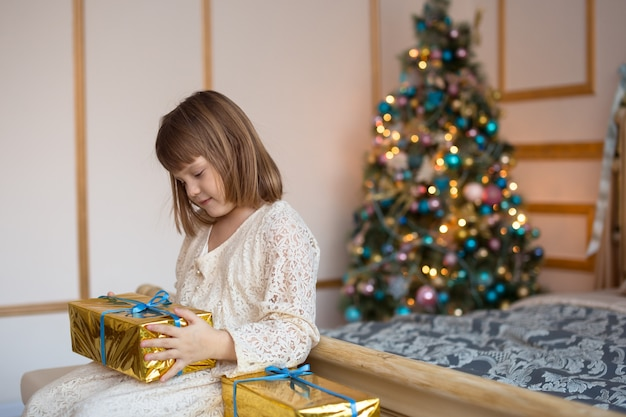 Child girl with gift on  bed, golden background, beautiful real bedroom